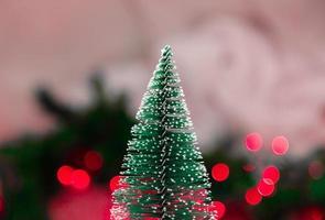 Árbol de Navidad en miniatura en el fondo borroso con luces de Navidad foto
