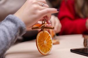 Mujeres haciendo adornos a mano con naranjas secas. foto