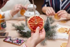 Mano de mujer sosteniendo una decoración de pomelos secos foto