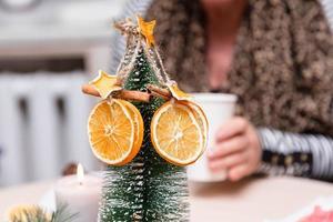 Estrellas anaranjadas secas de mandarina y canela colgando de un árbol de navidad foto