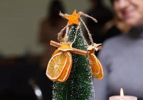 Estrellas naranjas secas de mandarina y canela decoración colgando de un árbol de navidad foto