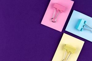 Bloc de notas con un juego de clips de papel de colores sobre fondo púrpura foto