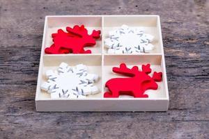 una caja blanca con compartimentos sobre un fondo de madera lleno de ciervos navideños y copos de nieve foto