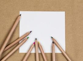 Blank notebook page with colorful pencils photo