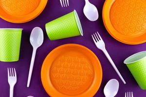 Recogida de residuos de plástico naranja verde sobre fondo púrpura foto