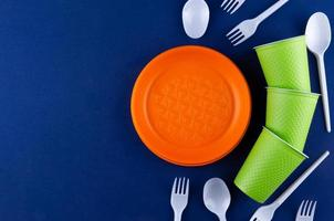 Orange, white and green packaging plastic products on blue background photo