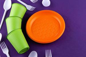 Plastic orange green waste collection on purple background Concept of plastic pollution and ecology problem photo