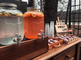 Location with summer drinks in glass jars or cupcake cans with a sign that says sweet love photo