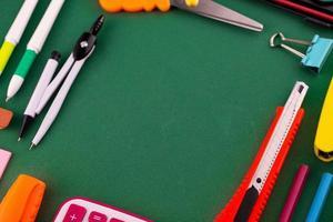 Material de oficina escolar papelería sobre un fondo verde escritorio con espacio de copia foto