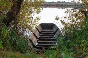 Barco de madera entre césped y árboles frente a un lago foto