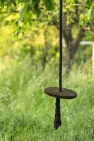 Columpio de un disco de madera que cuelga de una cuerda en un jardín descuidado foto