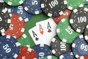 Casino tokens on green background with ace cards photo