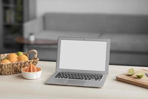 cítricos y portátil con pantalla en blanco sobre una mesa de madera foto
