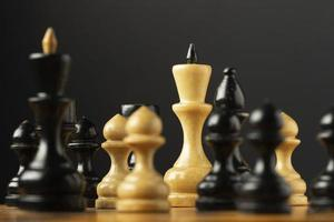 Black and white chess pieces on black background photo