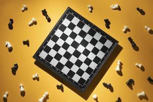 Piezas de ajedrez y tablero de ajedrez sobre fondo amarillo foto