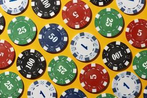 Casino tokens on yellow background photo