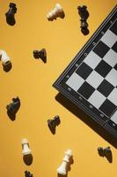 Chess pieces and chess board on yellow background photo