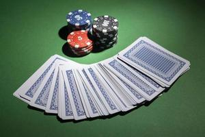 Casino tokens on green background with deck of cards photo