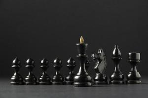 Black chess pieces on black background photo