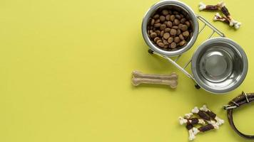 Top view on pet accessories still life with water and food bowls photo