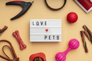 Top view on pet accessories still life concept with love pets text photo