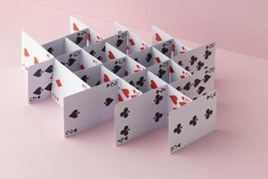 Structure made of cards on pink background photo