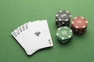 Royal flush and casino tokens on green background photo