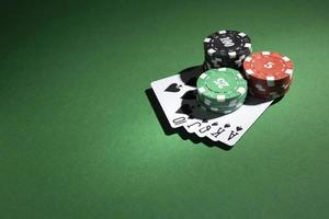 Stacked casino tokens and royal flush on green background photo