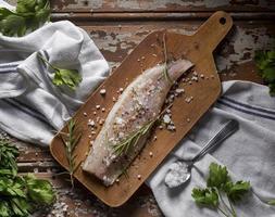 Pescado crudo con composición de condimentos para cocinar foto