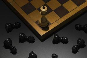 White king chess piece with fallen black pieces success concept photo