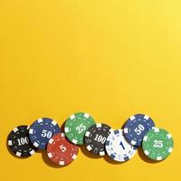 Casino tokens on yellow background photo