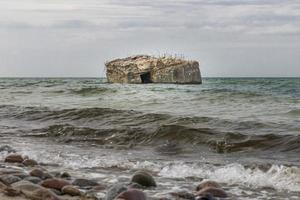 Old German bunker is rinsed out in the sea of the Baltic coast photo