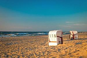 Beach chairs stand in the sunset on a beach on the Baltic Sea with sea photo