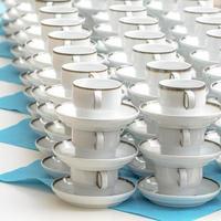Tazas de café con leche con platos de pie apilados en una fila foto