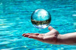 Glass ball hovers over a hand in front of water Background with mirrored sky and trees photo