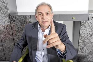 Middle aged man in a suit threatens his finger photo