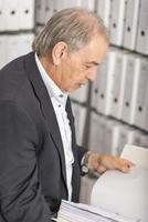 Middle aged man with white shirt is standing in front of a shelf wall with documents photo