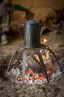Old metal coffee pot stands over a campfire photo