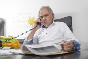 Senior man with white shirt phoning and scrolling in a file photo