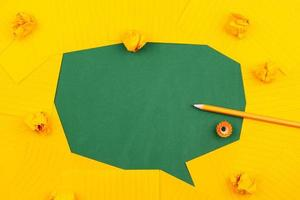 Orange sheets of paper lie on a green school board and form a chat bubble with pencil photo