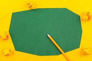 una hoja de papel naranja yace sobre una junta escolar verde foto