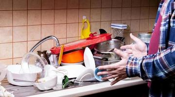 Shocked guy near a lot of dirty dishes lying in the sink photo
