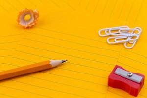 Orange sheets of paper pencil stationery and empty space for your text photo