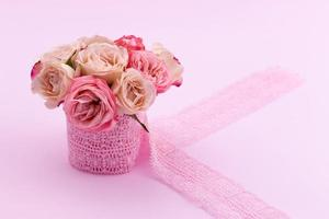 A bouquet of beautiful roses stands in a small bucket on a lace ribbon on a pink background with space for text photo