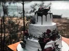 Hermoso pastel de bodas de crema blanca de tres niveles con fruta de granada y flores frescas sobre la mesa y velas foto