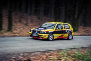 Yellow an black Volkswagen Golf hatchback during a car rally photo