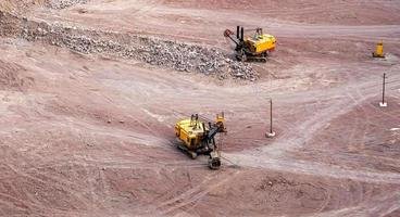 Excavator in a quarry extracting and moving stone photo