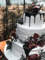 Hermoso pastel de bodas de crema blanca de tres niveles con fruta de granada y flores frescas foto