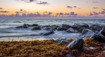 Black rocks beside body of water at golden hour photo
