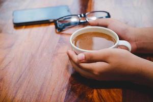 Una taza de café en una mesa de madera en una cafetería. foto